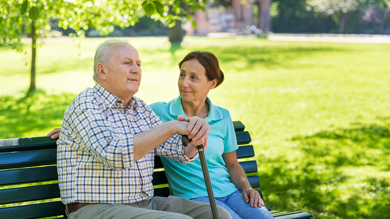 Caregiver – woman with senior man outdoors in the park